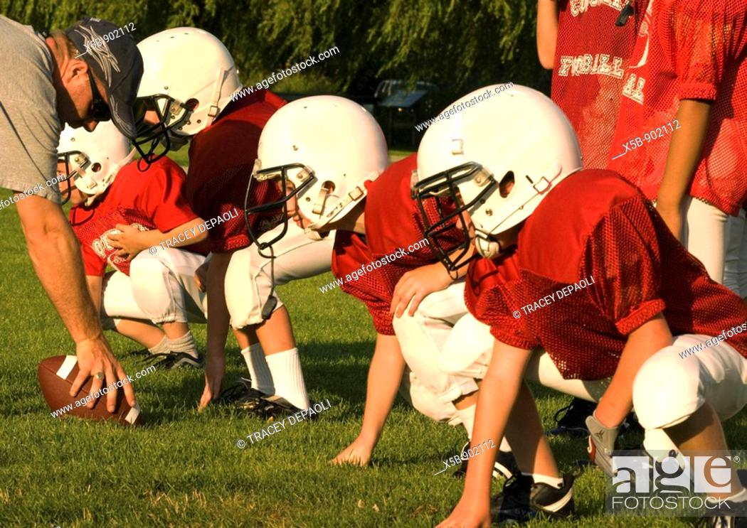 Imagen: 7 and 8 year old American Football players at practice  Atom division  On the line in practice  horizontal.