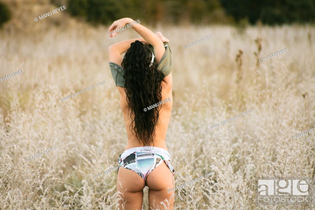 Imagen: Young brunette woman undressed in the field with 80's style.