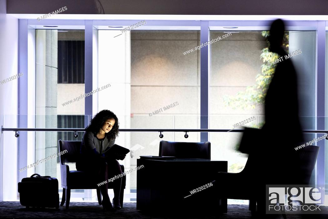 Photo de stock: A black businesswoman sitting in front of windows in a darkened lobby area of a convention centre.