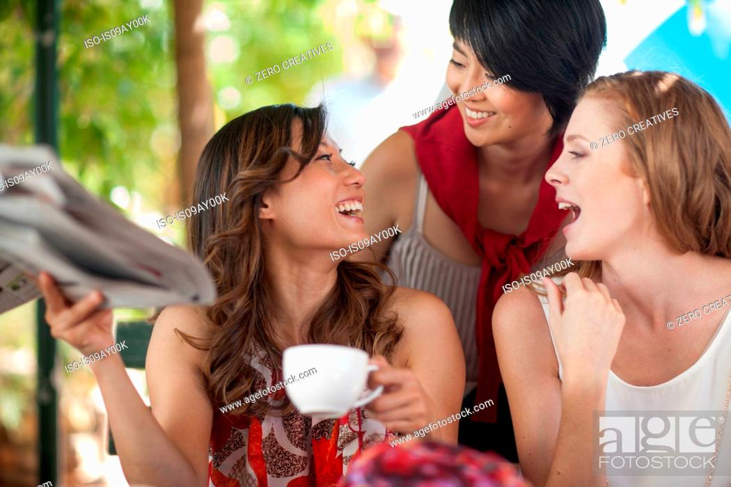 Stock Photo: Three female friends laughing together at sidewalk cafe in city.