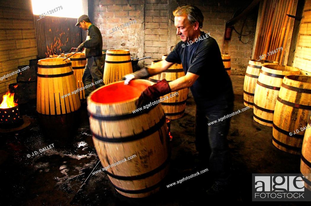 Stock Photo: Master cooper Francis M. working on burning of barrels at cooperage, at Marmande, Lot-et-Garonne, Aquitaine, France.
