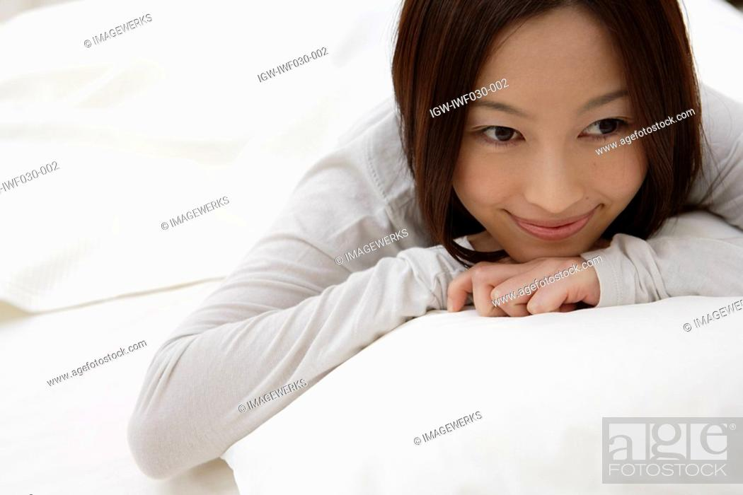 Stock Photo: A young woman lying on a bed.