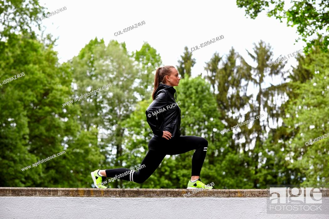 Stock Photo: Young woman training, lunging on top of wall.