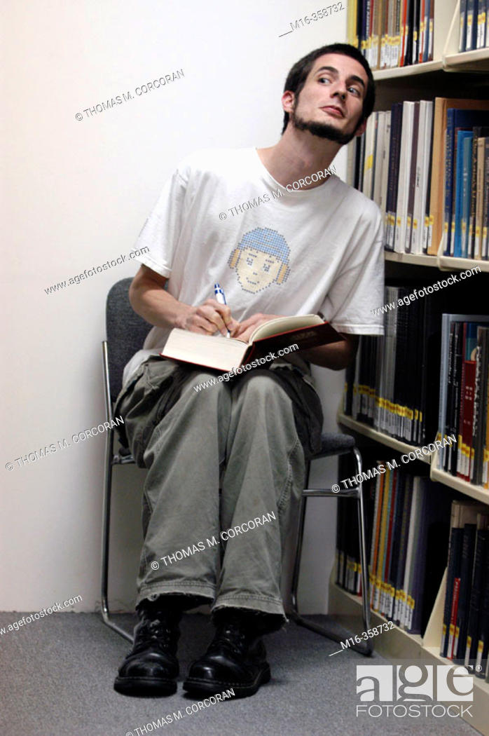 Stock Photo: Dave, a student at the Corcoran College in Washington DC, suspiciously takes notes in the reference section of the school's library.