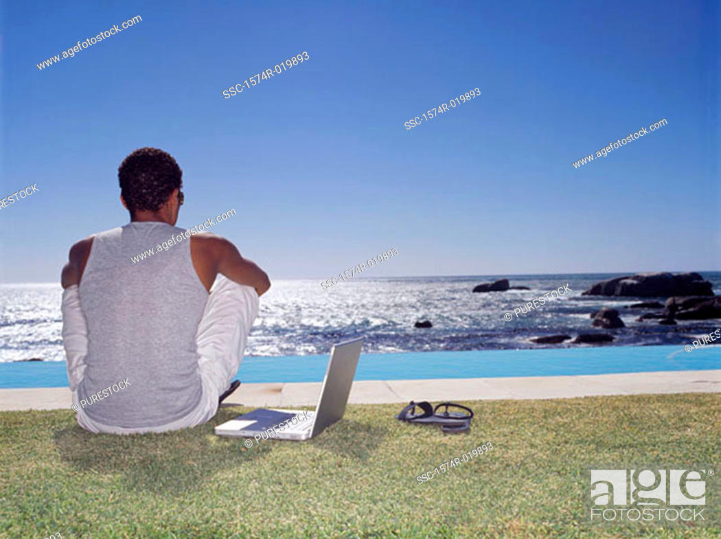 Stock Photo: Rear view of a young man sitting on a lawn with a laptop beside him.