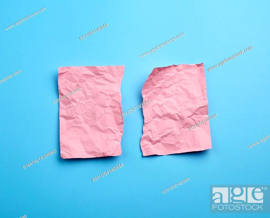 Stock Photo: crumpled pink sheet of paper torn in two on a blue background. Paper piece torn edge.