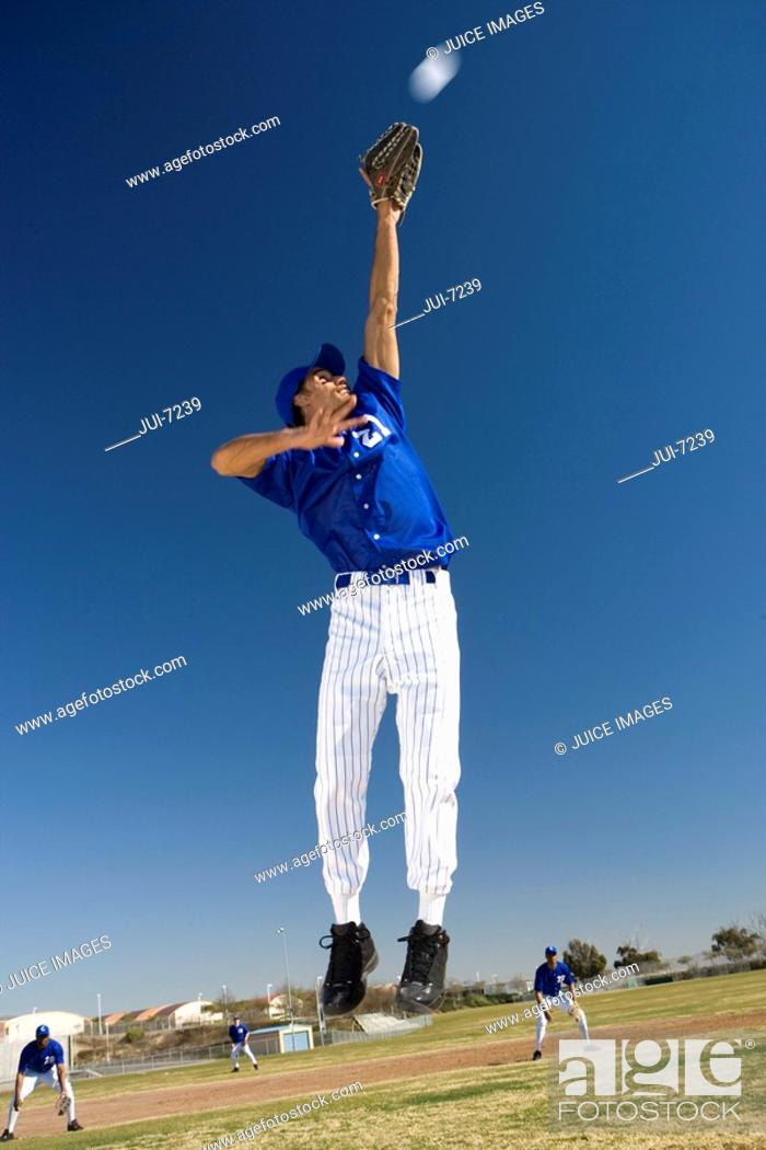 Stock Photo: Baseball player, in blue uniform, jumping up to catch ball in protective glove during competitive game surface level, tilt.