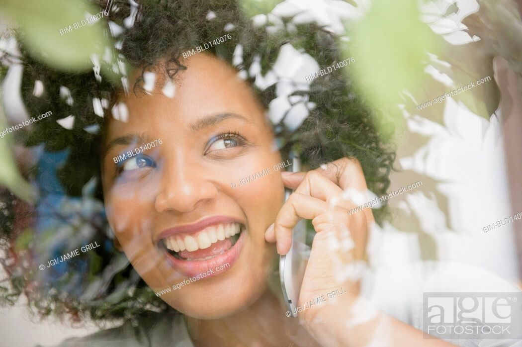 Stock Photo: Smiling woman talking on cell phone near window.