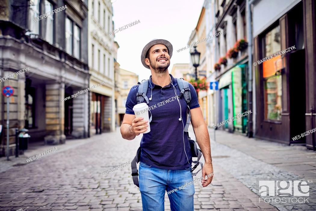 Stock Photo: Traveler with backpack walking down city street and holding coffe.