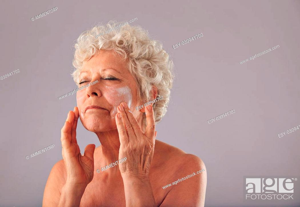 Stock Photo: Portrait of senior woman applying lotion on her face against grey background. Mature caucasian woman applying anti-wrinkle face cream.