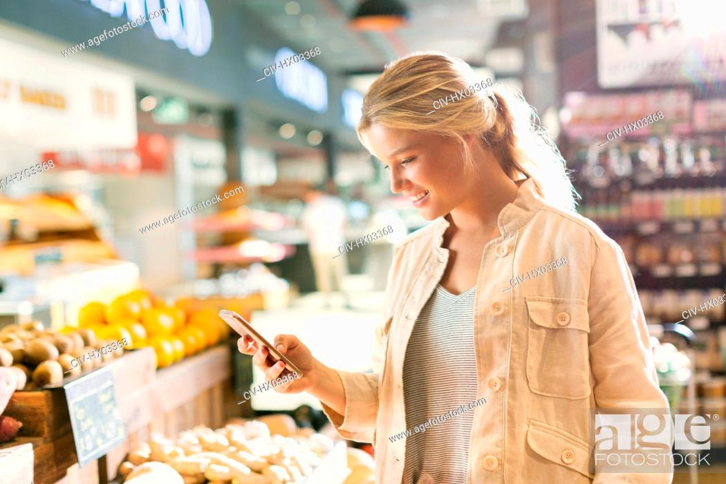 Stock Photo: Young woman using cell phone in grocery store market.
