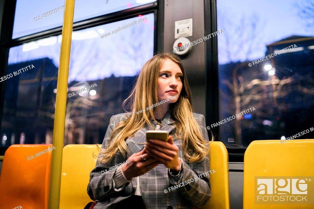 Stock Photo: Young woman with long blond hair sitting in train carriage with smartphone at dusk.