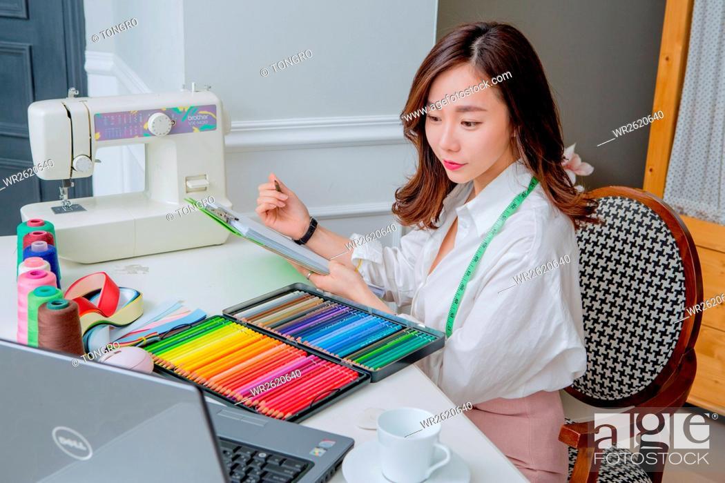 Stock Photo: Female fashion designer working.