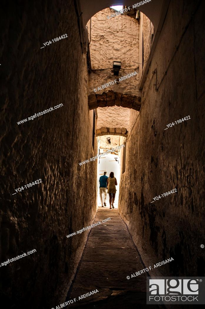 Stock Photo: A couple walk through the streets of Sitges, Barcelona, Spain.