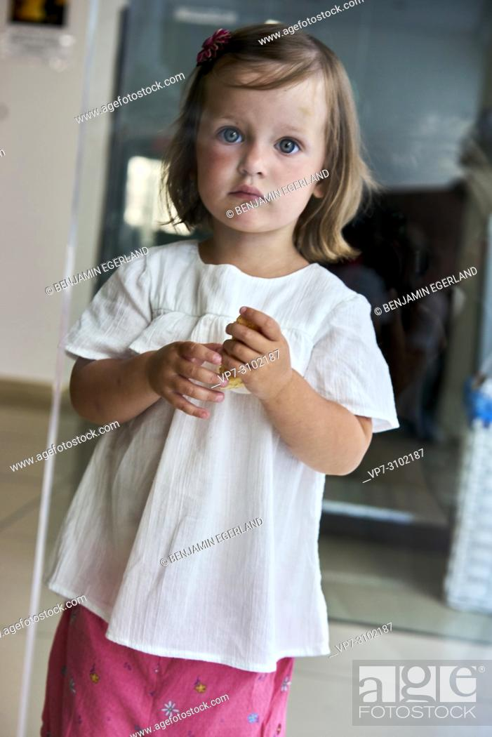 Imagen: candid portrait of young girl at home, holding in her hands something to eat.