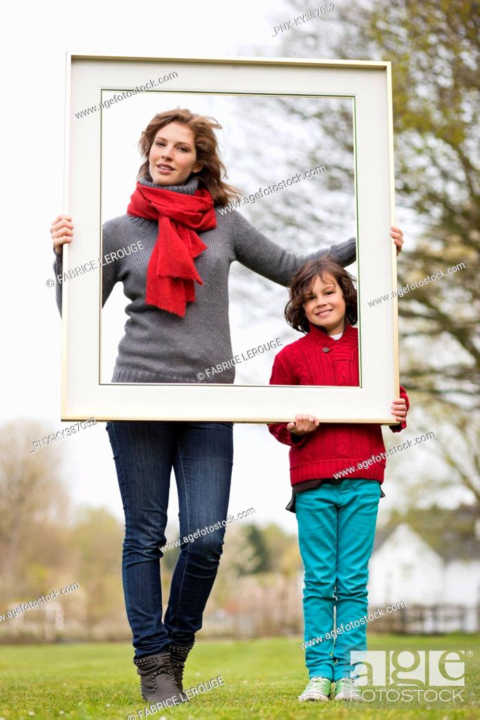Stock Photo: Woman and her son holding a picture frame in a park.