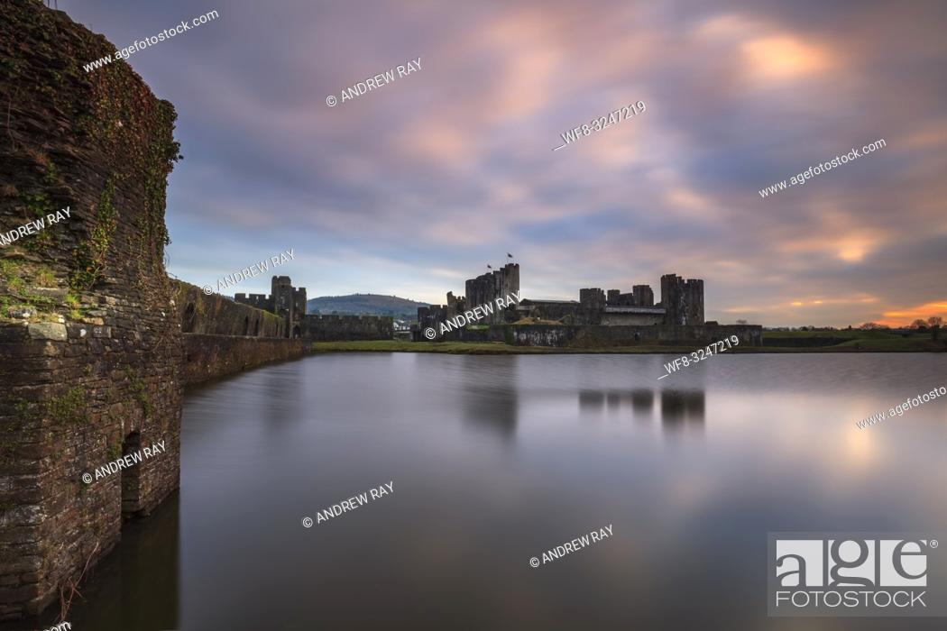 Stock Photo: Caerphilly Castle in South Wales reflected in the lake at sunset in mid February. The image was carefully composed with the walls on north bank leading the.