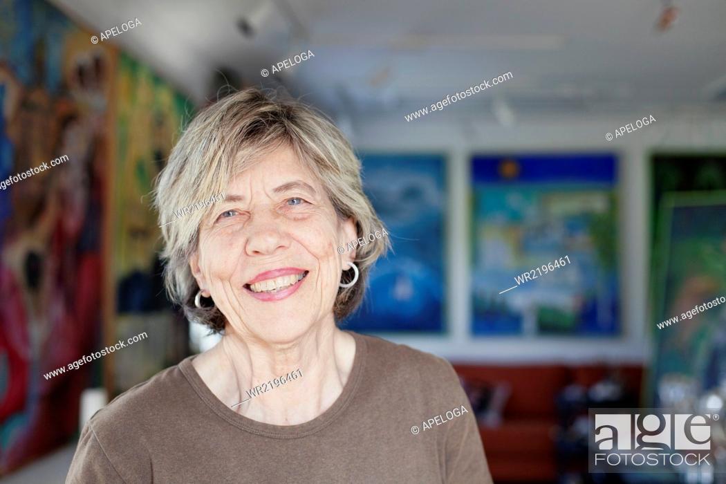 Stock Photo: Portrait of smiling senior female artist in art studio.