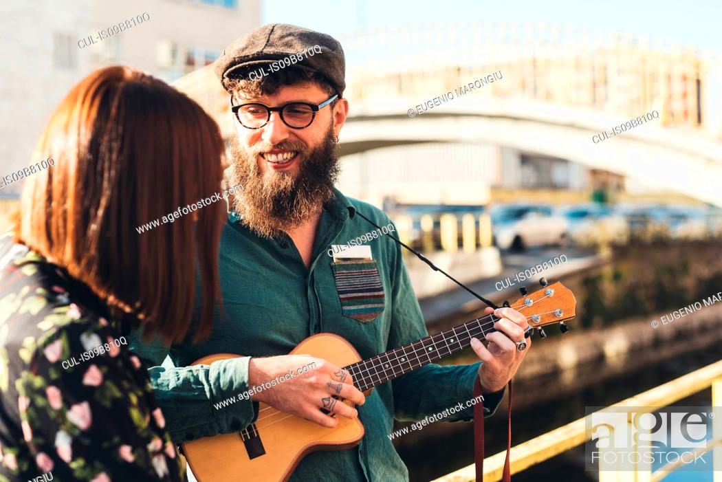 Imagen: Hipster couple playing ukulele by canal.