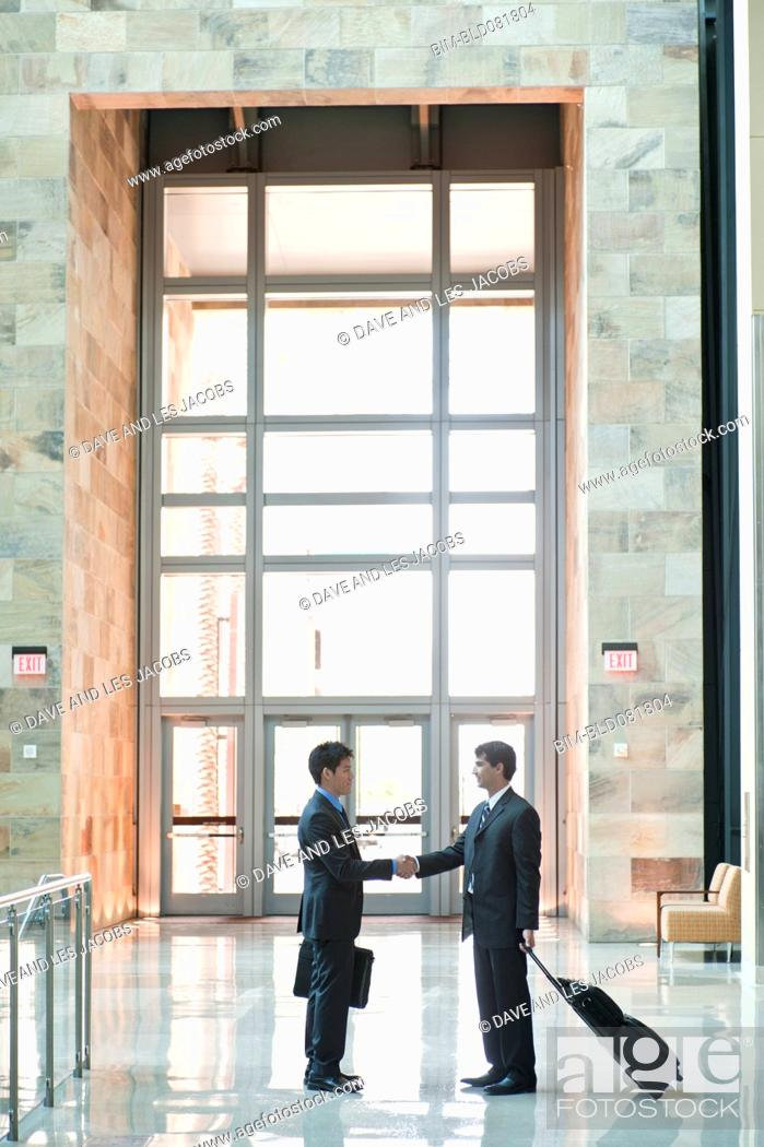 Stock Photo: Traveling businessmen shaking hands in building lobby.