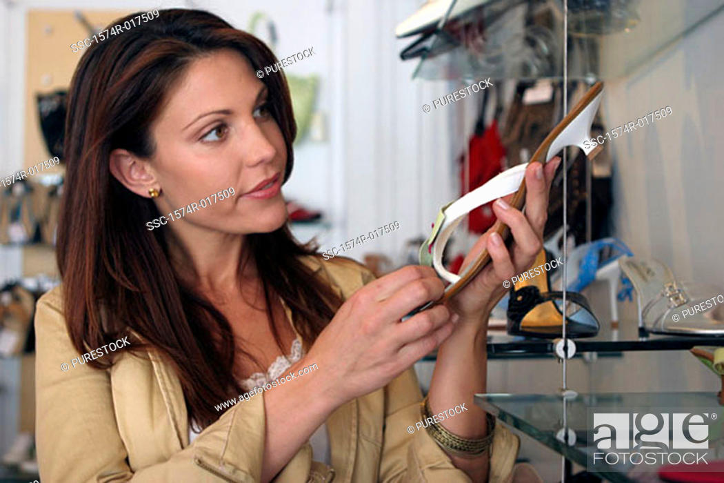 Stock Photo: Young woman holding a sandal in a shoe store.