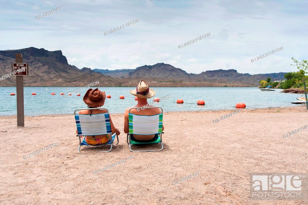 Stock Photo: Couple sitting on deck chairs, Lake Havasu, Arizona, USA.