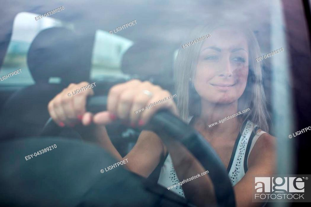 Stock Photo: Woman driving a car - female driver at a wheel of a modern car, looking happy, smiling with a relaxed smile (shallow DOF; color toned image).