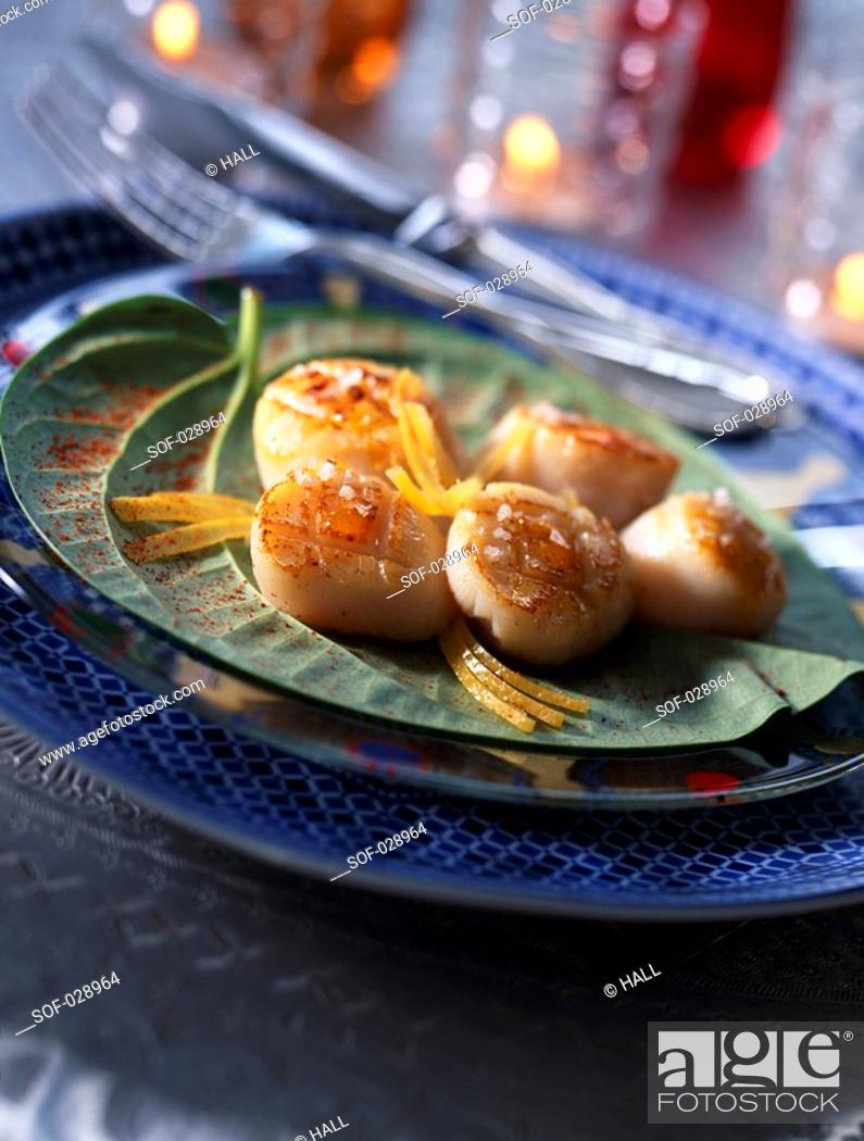 Stock Photo: Pan-fried scallops with harissa oil and confit lemon.