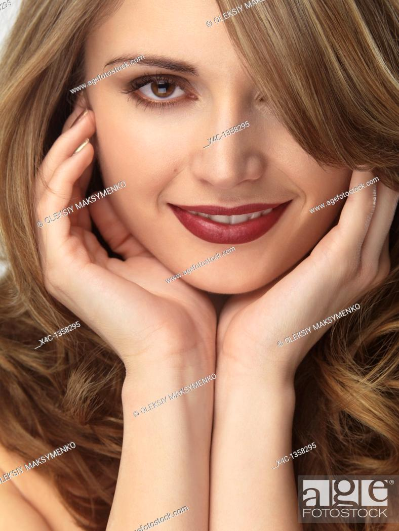 Stock Photo: Portrait of a beautiful young smiling woman.