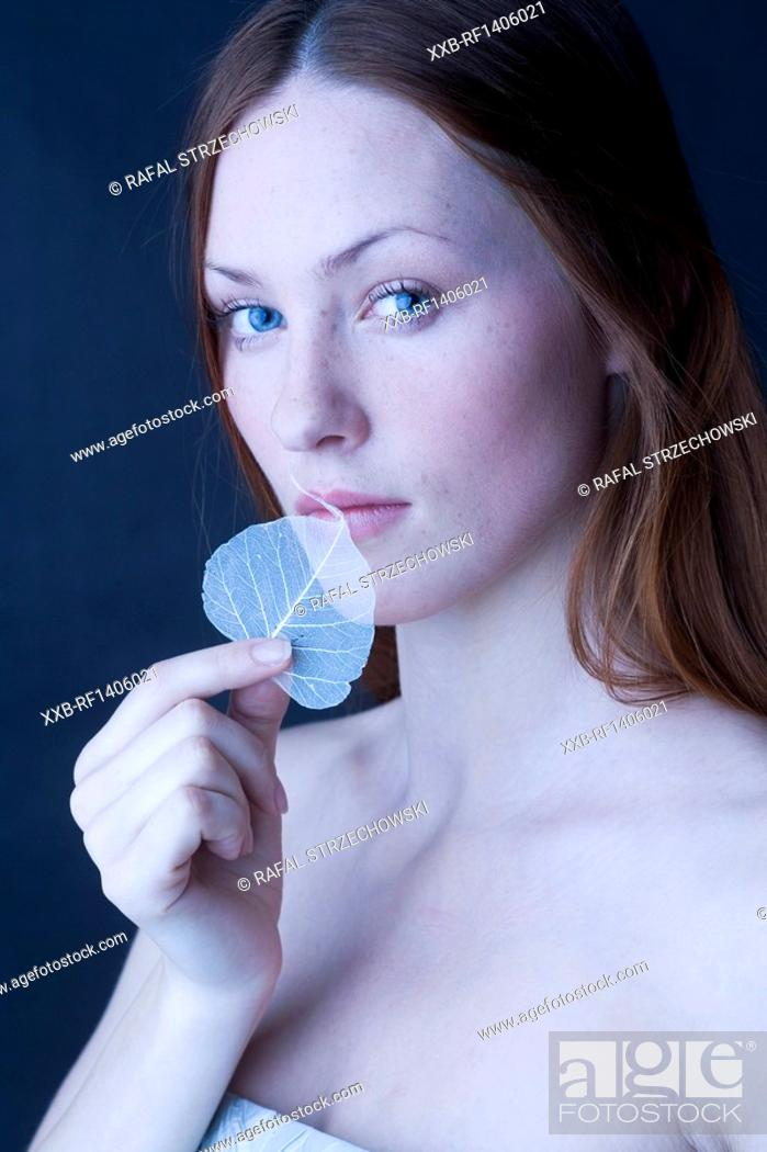 Stock Photo: woman covering lips with leaf.