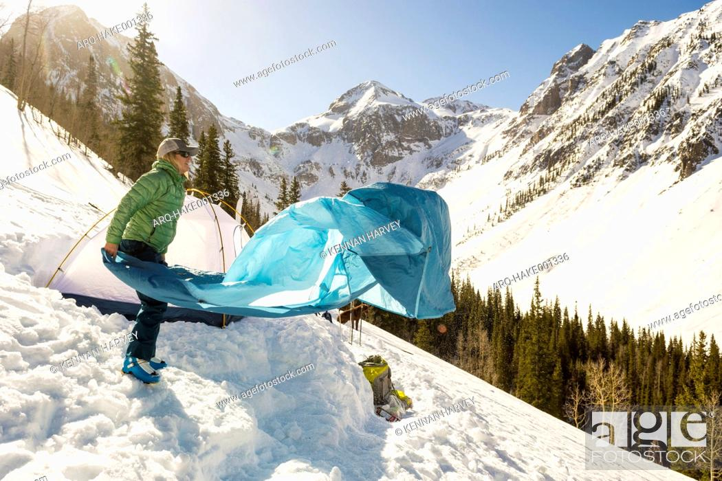 Imagen: Adult woman packing up tent after winter camping in snowcapped Arastra Gulch mountain pass, Silverton, Colorado, USA.