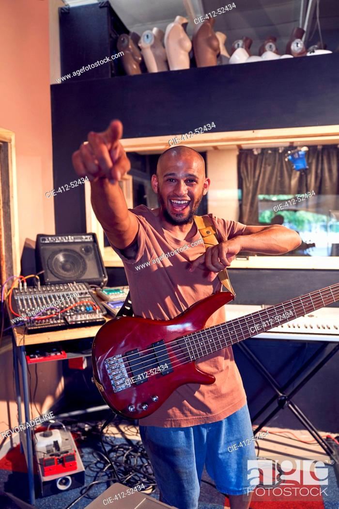 Stock Photo: Portrait enthusiastic male musician playing guitar in recording studio.