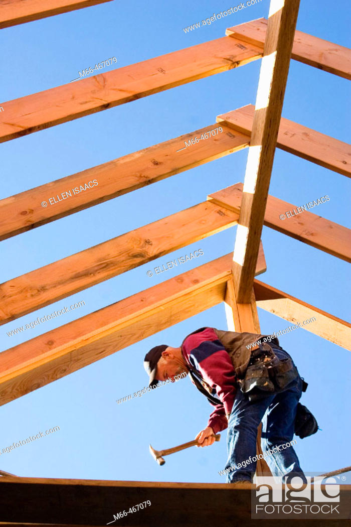Stock Photo: Carpenter hammering trimmer to center post while standing below the framing of the roof rafters at a construction site.