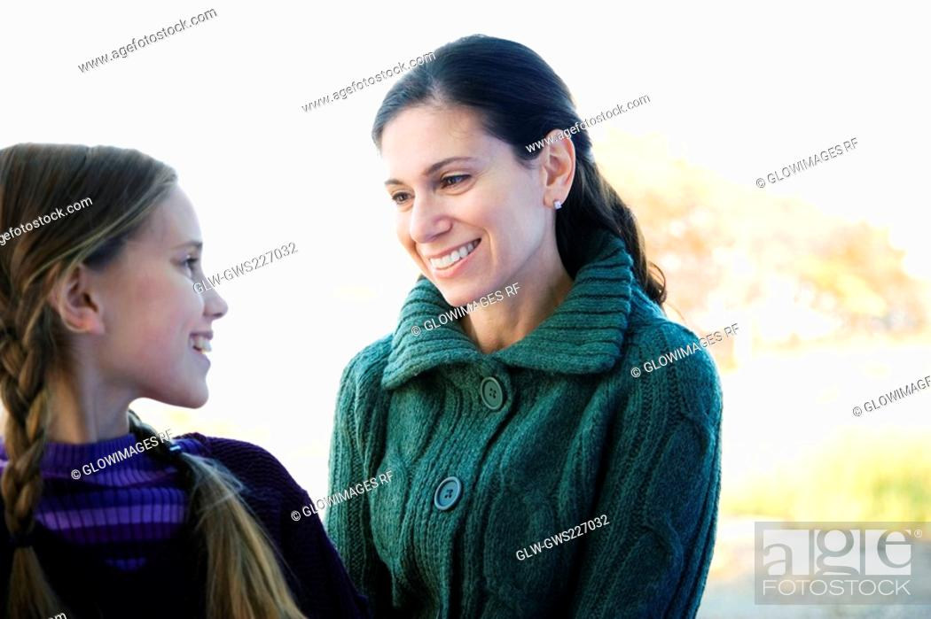 Stock Photo: Mid adult woman looking at her daughter and smiling.