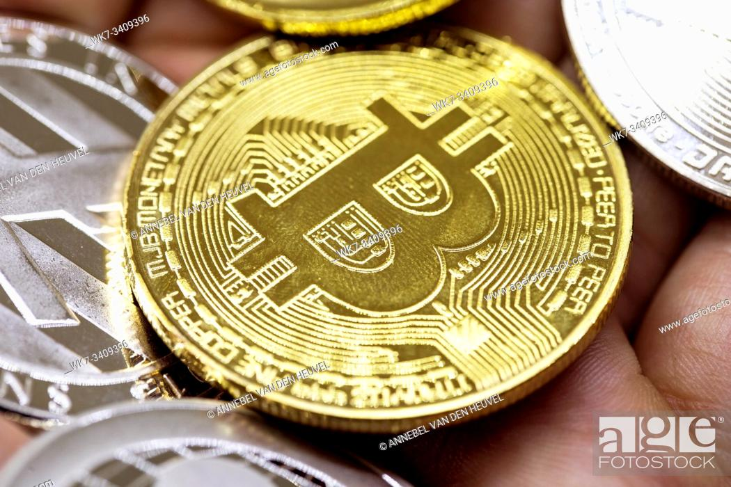 Stock Photo: Golden Bitcoin in a man hand, Digitall symbol of a new virtual currency with black and white background.