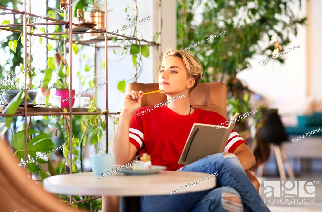 Stock Photo: teenage girl with notebook at coffee shop or cafe.