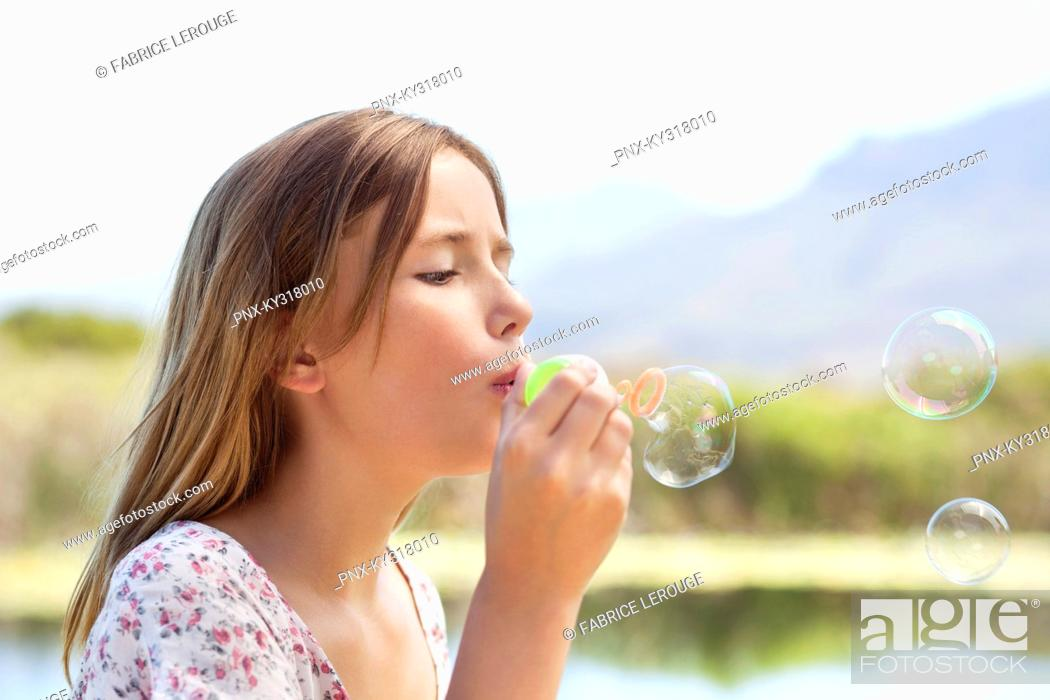 Stock Photo: Close-up of a girl blowing bubbles.