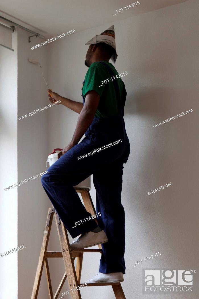 Stock Photo: A man standing on a ladder and painting a wall.