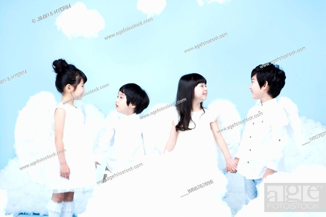 Stock Photo: four kids with looks of angels on the clouds.