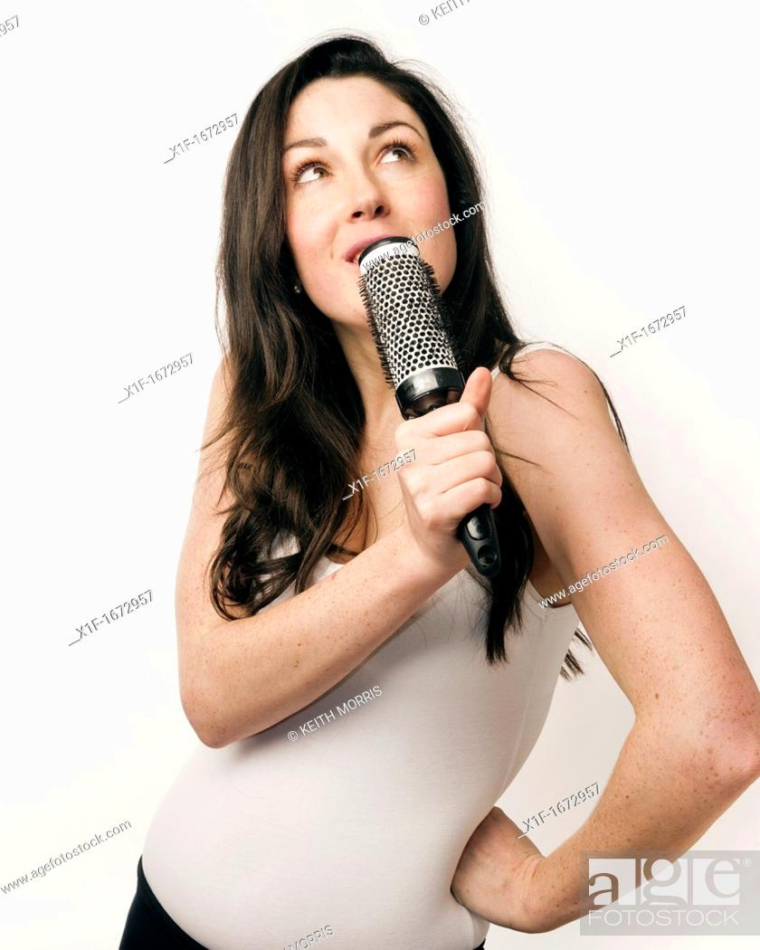 Stock Photo: A young woman with brown hair and eyes miming singing into her hairbrush.