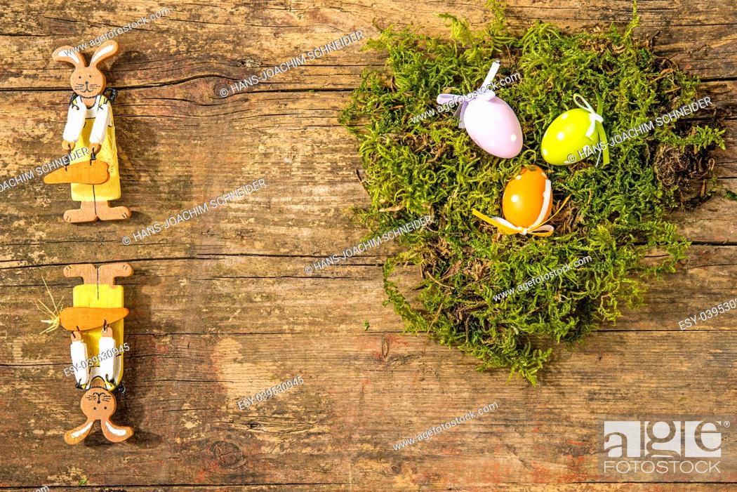 Stock Photo: easter nest with painted eggs and easter bunnies.