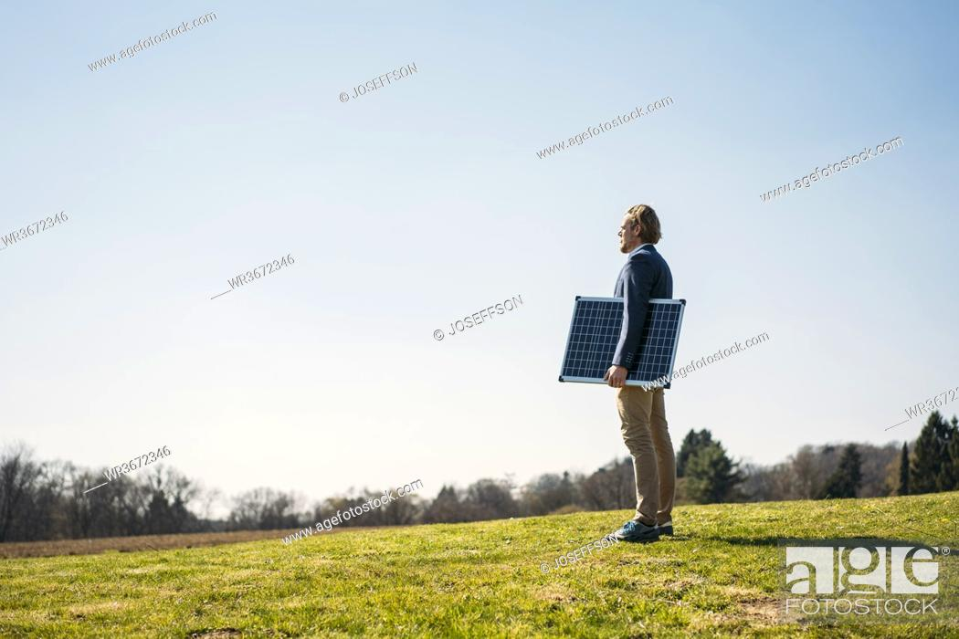 Stock Photo: Businessman holding solar panel while standing on grass and looking away at park against clear sky during sunny day.