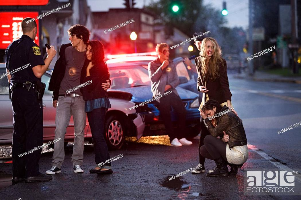 Stock Photo: Young people and police officer at scene of car crash.