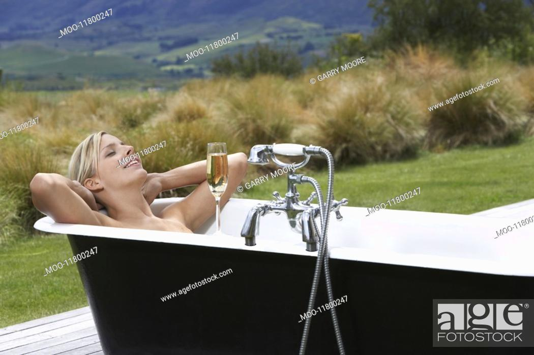 Stock Photo: Woman taking bath with champagne on porch in countryside.