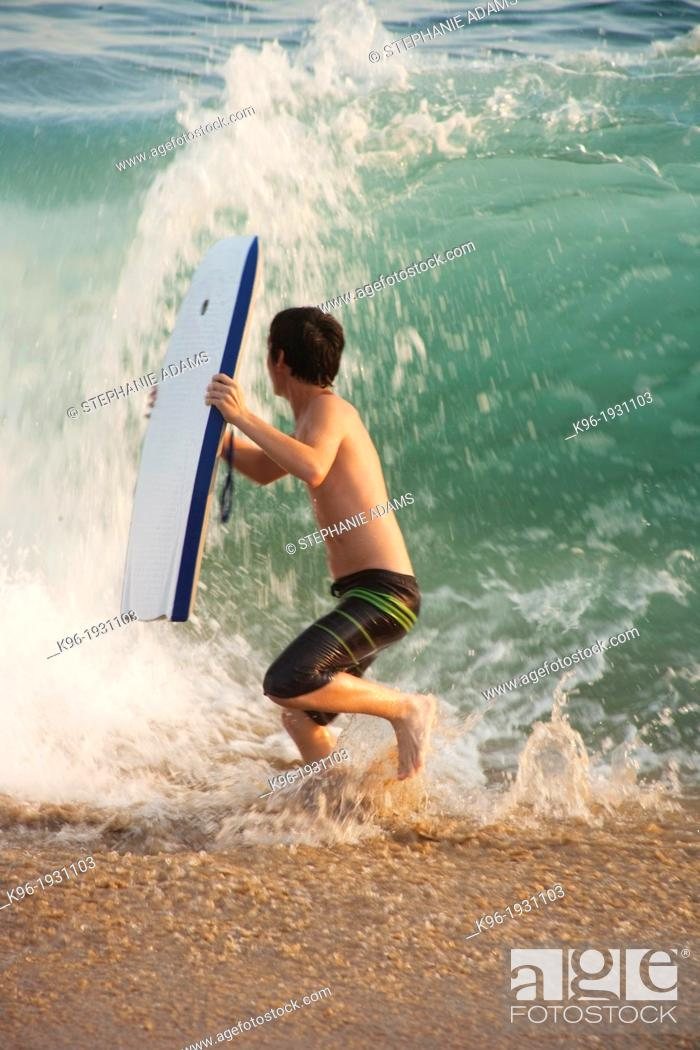 Stock Photo: boy running from a big ocean wave.