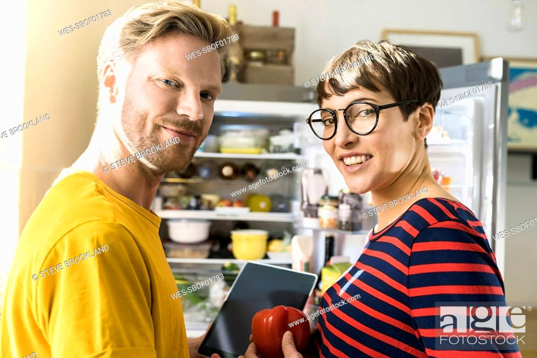 Stock Photo: Portrait of couple with tablet in front of their fridge doing online shopping for groceries.