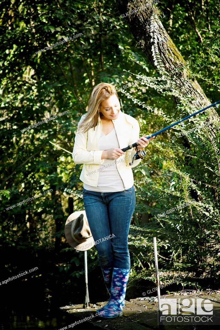Stock Photo: Woman fly-fishing in a river.