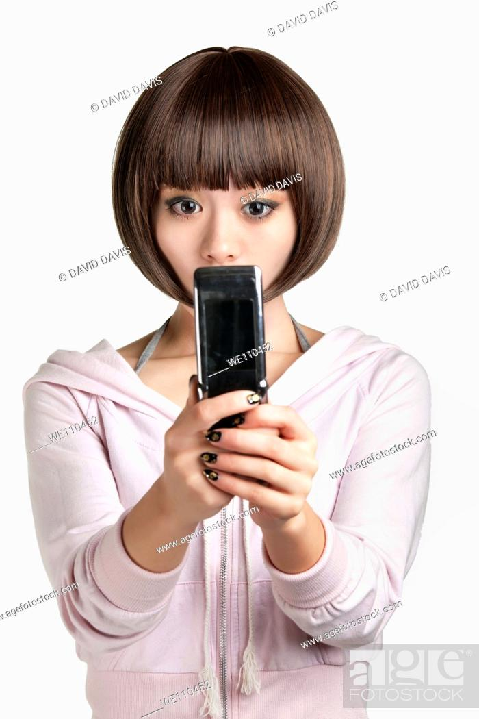 Stock Photo: Beautiful Chinese woman using a cell phone on a white background.
