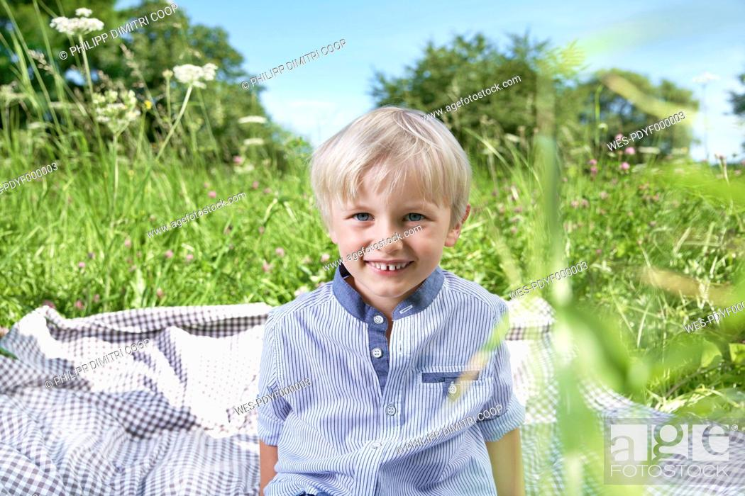 Stock Photo: Germany, Cologne, Boy sitting on blanket in meadow, smiling, portrait.