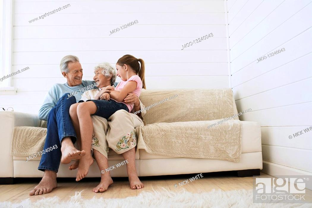 Stock Photo: Senior man and woman sitting with granddaughter on woman's knee on couch.